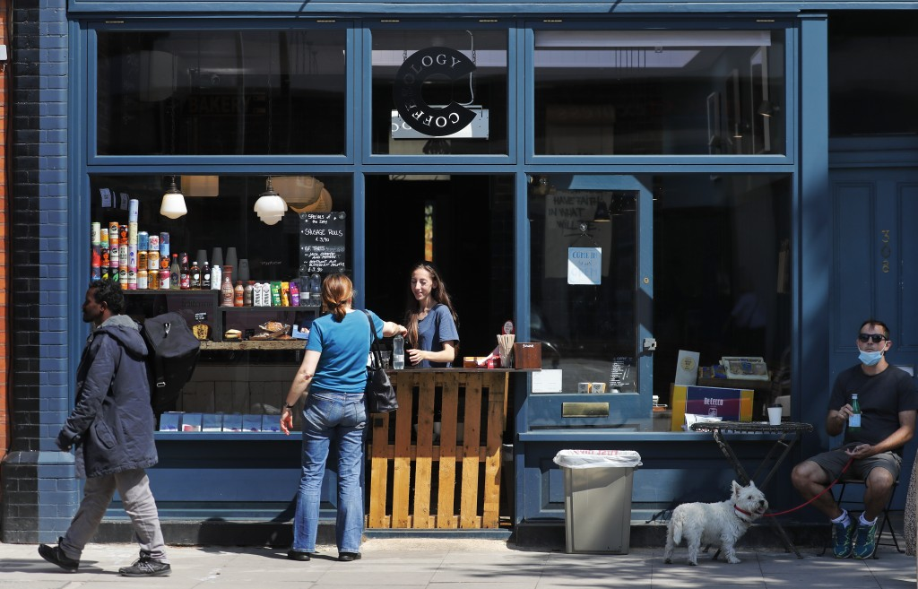 People buy food and drinks at a restaurant currently only doing take away food in London, Tuesday, June 23, 2020. The closing of restaurants, hair cut...