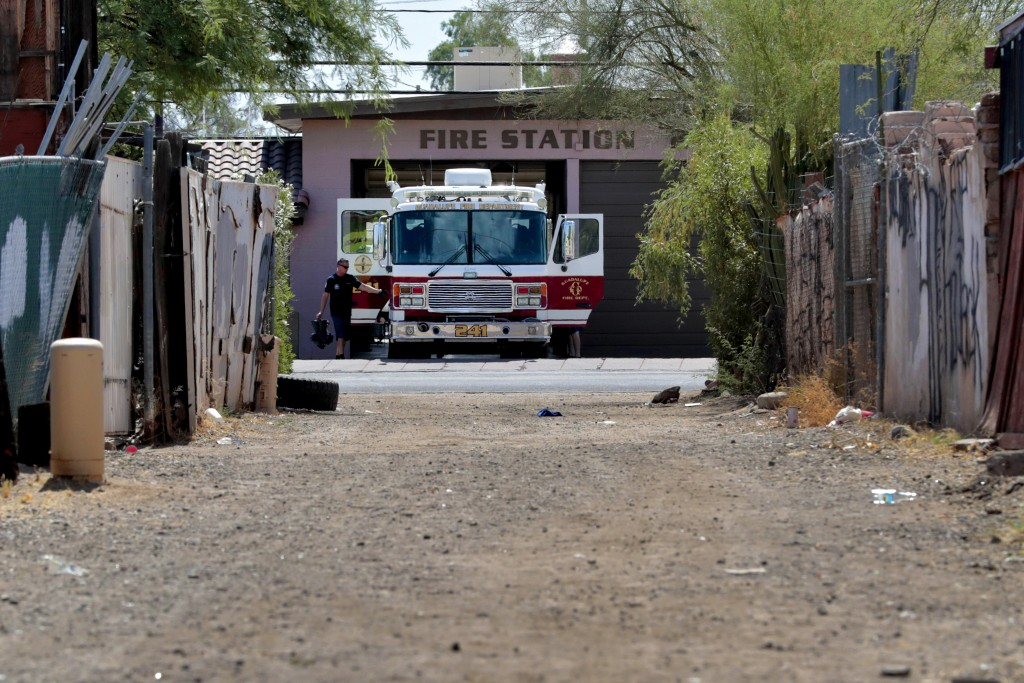 In this Saturday, June 13, 2020, photo, Guadalupe firefighters prepare their engine prior to a call in Guadalupe, Ariz. As the coronavirus spreads dee...