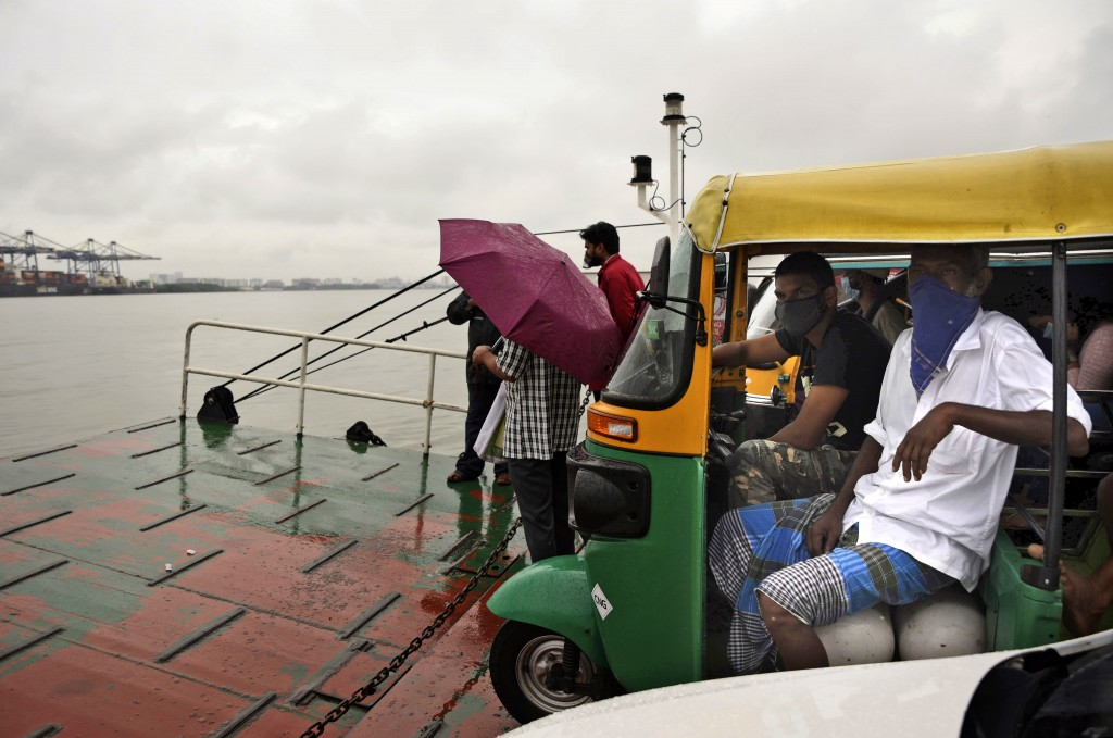 Commuters wearing masks as a precaution against the coronavirus travel in a ferry during rain in Kochi, Kerala state, India, Monday, June 22 2020. Ind...
