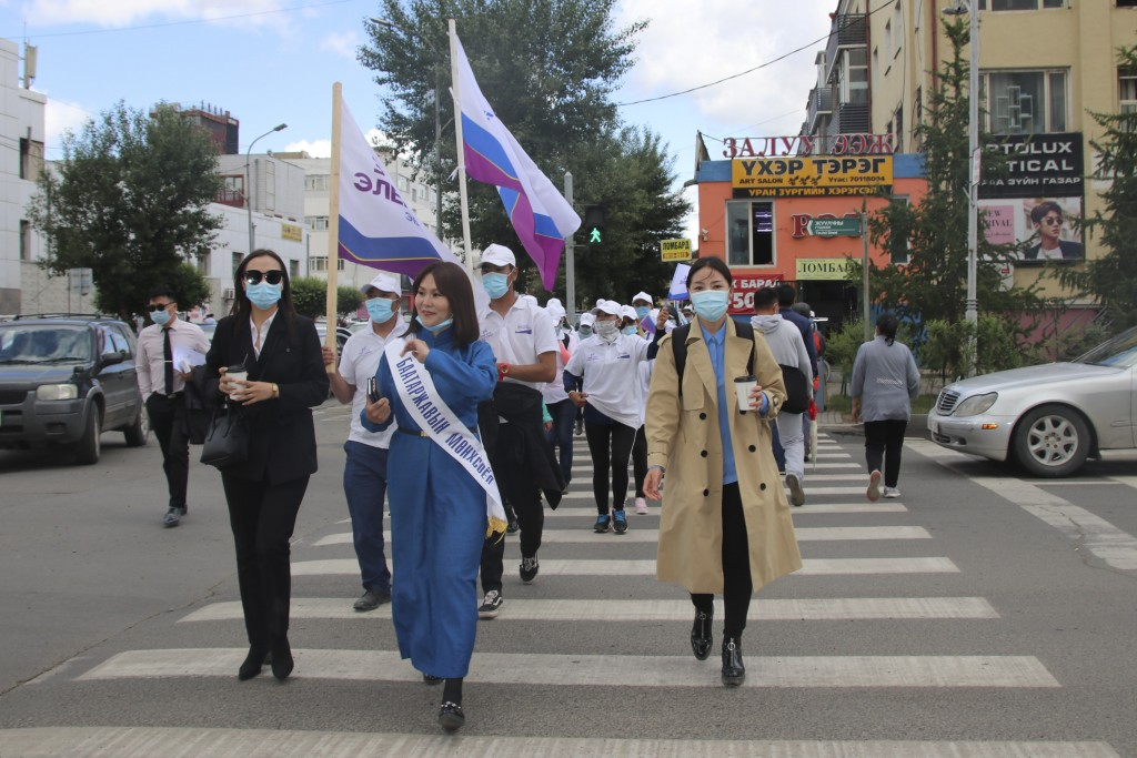 "Munkhsoyol Baatarjav, female candidate of ""Right person-Electorate"" coalition led by National Labor Party, wearing long blue robe and white ribbon, wa..."