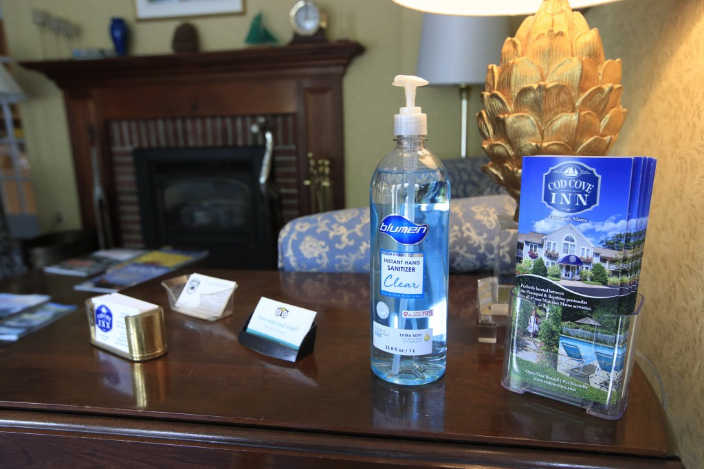 In this Wednesday, June 10, 2020, photo, hand sanitizer is provided for guests in the lobby of the Cod Cove Inn in Edgecomb, Maine. Home-bound travele...