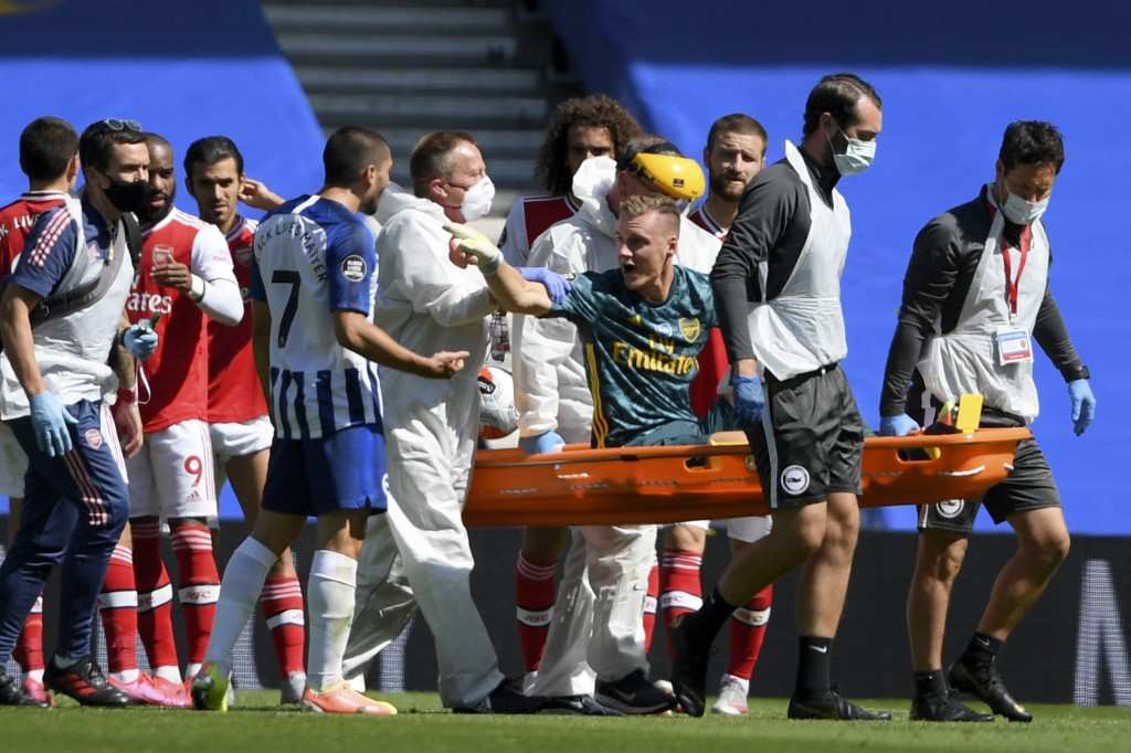 Arsenal's goalkeeper Bernd Leno gestures at Brighton's Neal Maupay as he leaves the pitch on a stretcher after getting injured during the English Prem...