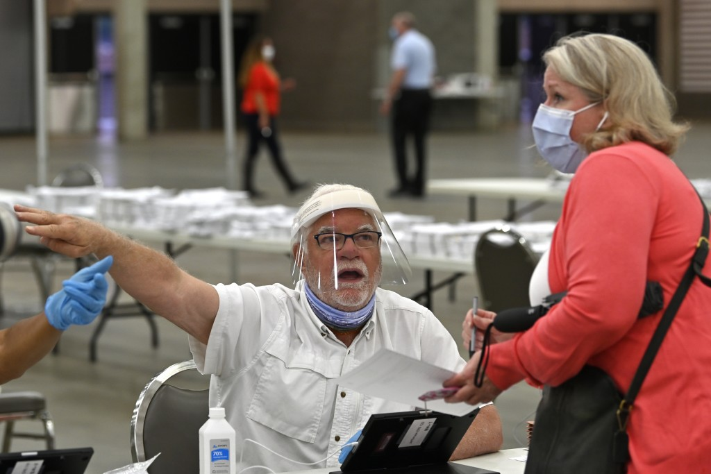 Poll workers instruct a voter on where to go to fill out their ballot during the Kentucky primary at the Kentucky Exposition Center in Louisville, Ky....