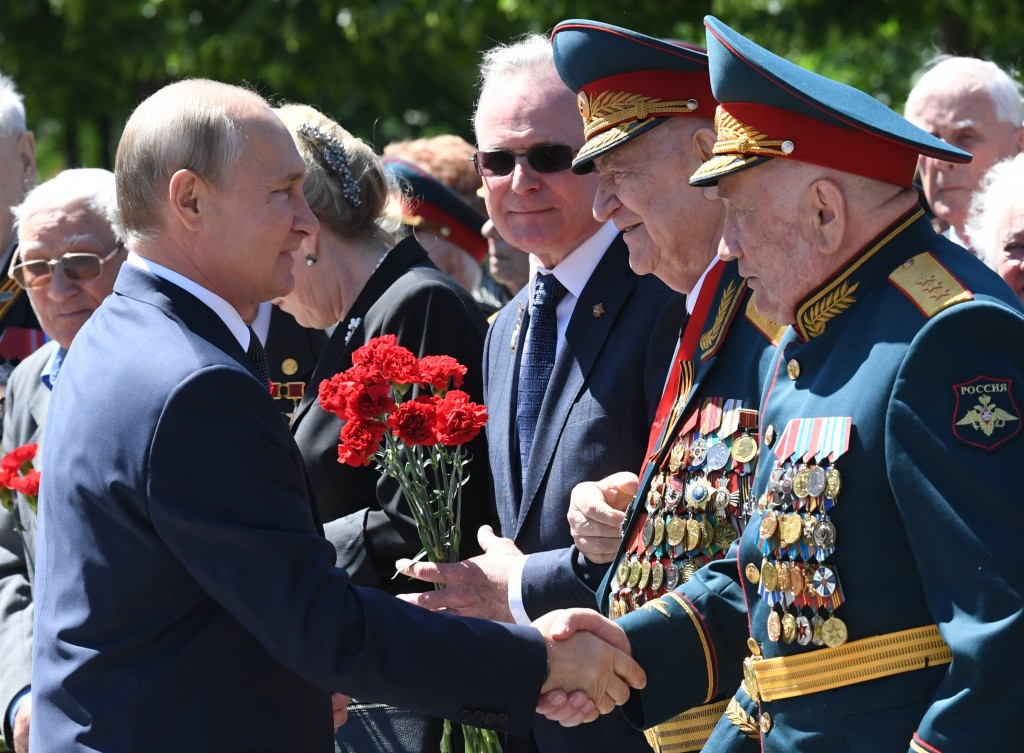 FILE - In this file photo taken on Monday, June 22, 2020, Russian President Vladimir Putin, left, greets WWII veterans during a wreath laying ceremony...