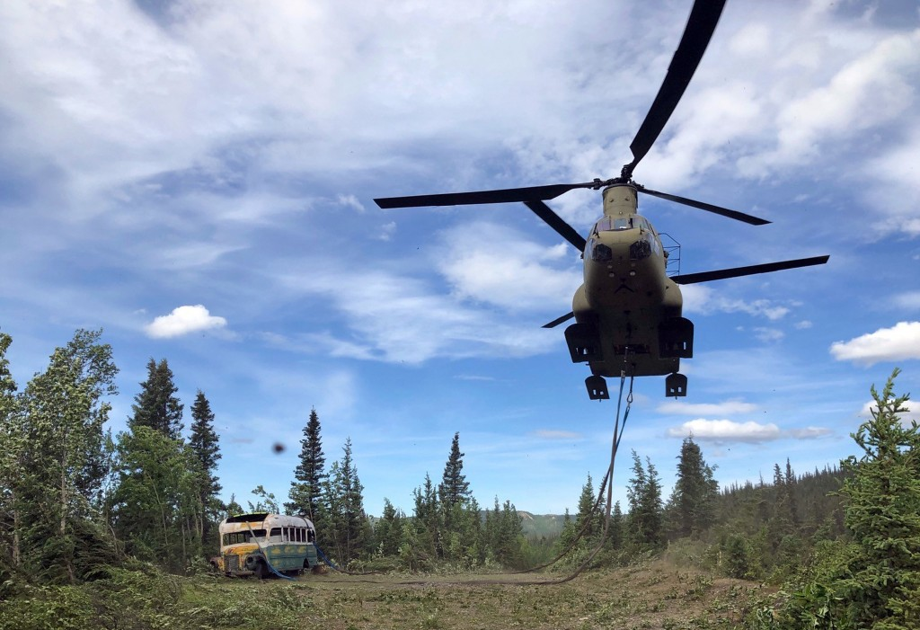 In this photo released by the Alaska National Guard, Alaska Army National Guard soldiers use a CH-47 Chinook helicopter to removed an abandoned bus, p...