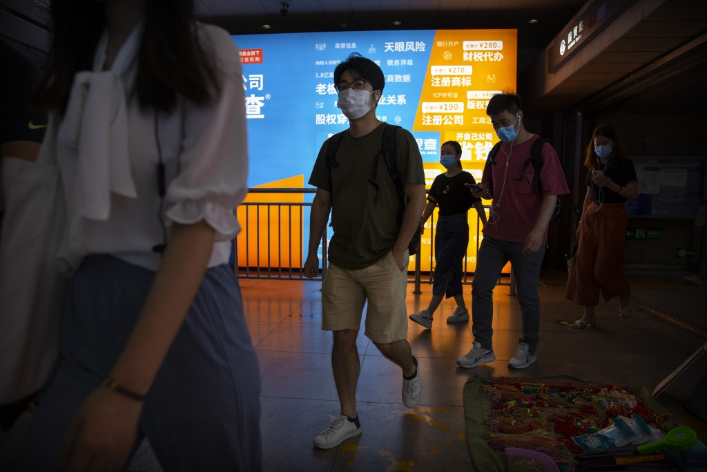Commuters wear face masks to protect against the new coronavirus as they walk through a subway station in Beijing, Tuesday, June 23, 2020. China repor...