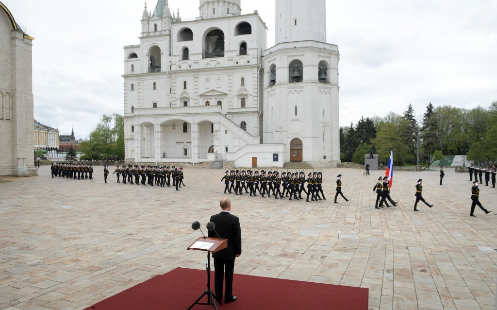 FILE - In this file photo taken on Saturday, May 9, 2020, Russian President Vladimir Putin, back to a camera, watches the honour guard of the Presiden...