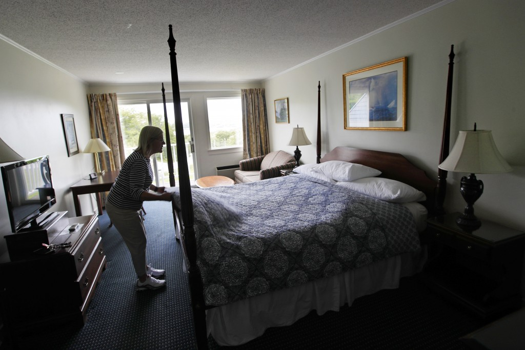 In this Wednesday, June 10, 2020, photo, Cod Cove Inn owner Jill Hugger adjusts a bedspread in a room at her inn in Edgecomb, Maine. During the corona...