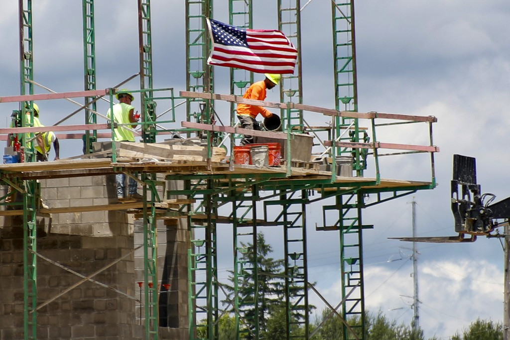 FILE - In this June 11, 2020, file photo workers on scaffolding lay blocks on one of the larger buildings at a development site where various resident...