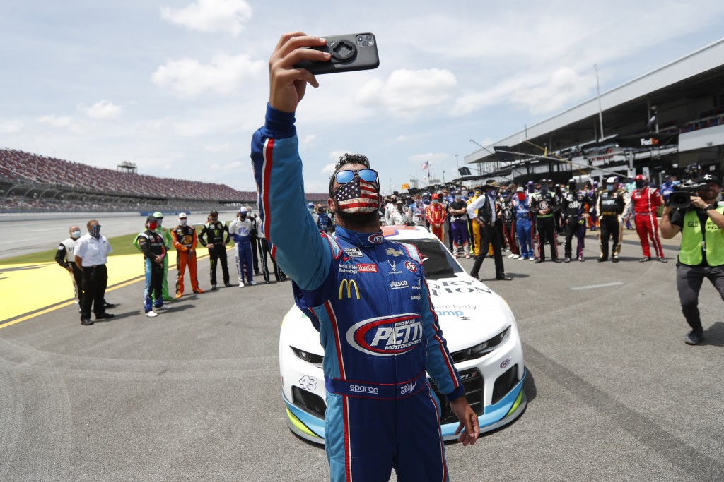 Driver Bubba Wallace takes a selfie with himself and other drivers that pushed his car to the front in the pits of the Talladega Superspeedway prior t...