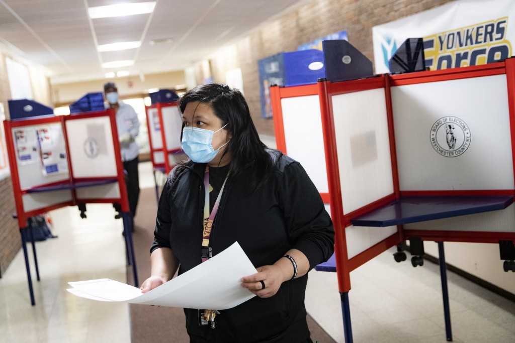 A voter wears a protective mask while casting their vote in New York's primary election at a polling site inside Yonkers Middle/High School, Tuesday, ...