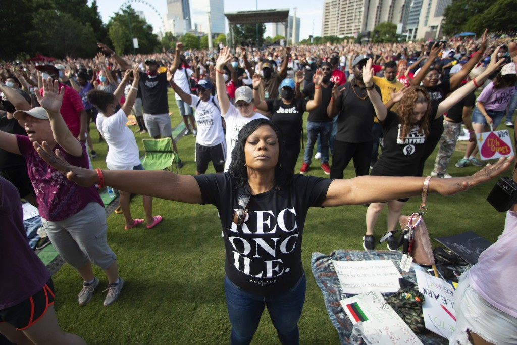 ADDS DESCRIPTION OF ONERACE MOVEMENT - A woman prays during an event hosted by OneRace Movement at Atlanta's Centennial Olympic Park to commemorate Ju...