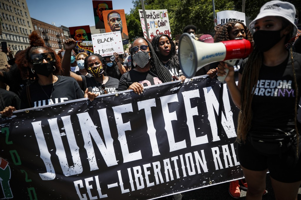 Protesters chant as they march after a Juneteenth rally at the Brooklyn Museum, Friday, June 19, 2020, in the Brooklyn borough of New York. Juneteenth...