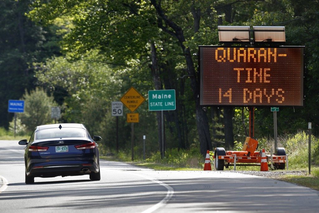 In this Wednesday, June 10, 2020, photo, a sign in Gilead, Maine, near the border with New Hampshire, warns visitors entering Maine that they are requ...