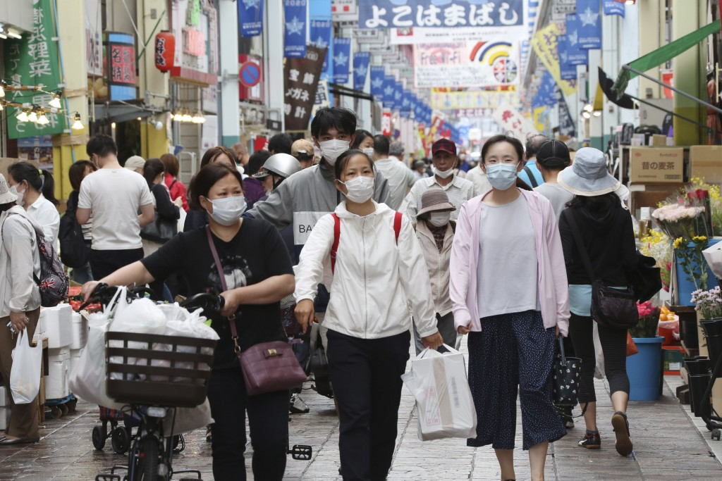 People wearing face masks shop at a mall in Yokohama, near Tokyo, Tuesday, June 23, 2020. Japan's economy is opening cautiously, with social-distancin...