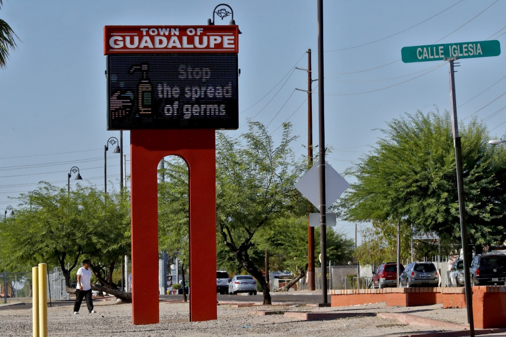 Tn this Thursday, June 18, 2020, photo, a sign encourages hand washing in Guadalupe, Ariz. As the coronavirus spreads deeper across America, it's rava...