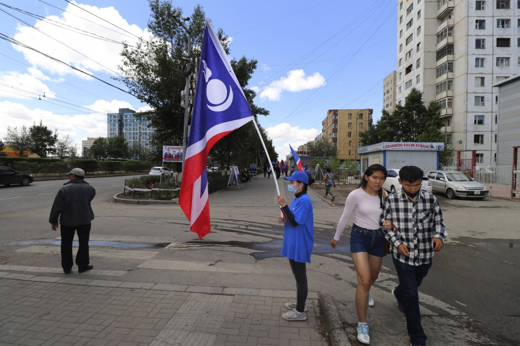 A couple walks past a Democratic Party campaign worker holding the party flag in the Songinokhairkhan district on the outskirts of Ulaanbaatar, Mongol...
