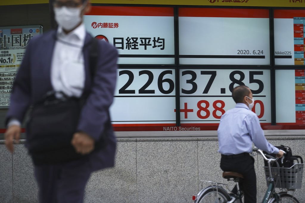 A man walks past an electronic stock board showing Japan's Nikkei 225 index at a securities firm in Tokyo Wednesday, June 24, 2020. Asian shares were ...