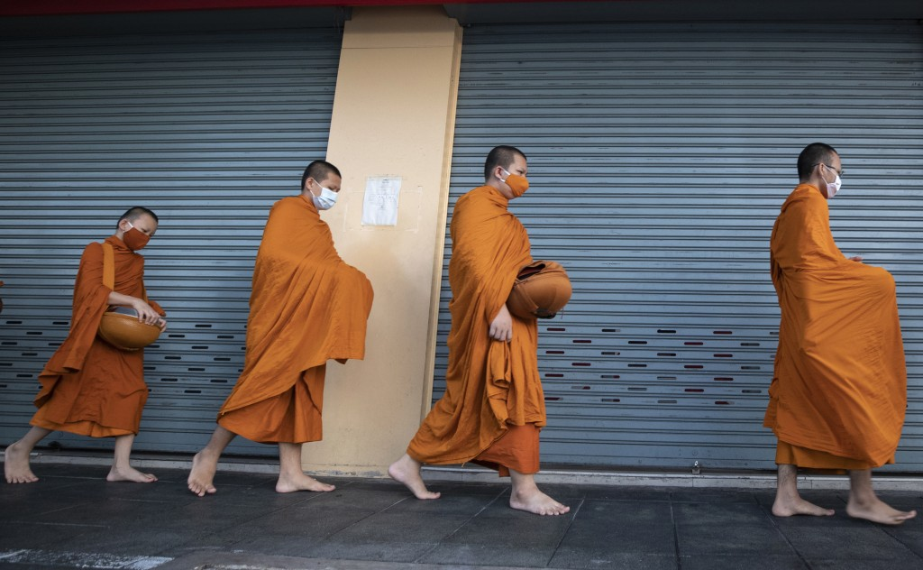 Thai Buddhist monks wearing face masks to help curb the spread of the coronavirus walk to collect alms from devotees in Bangkok, Thailand, Wednesday, ...