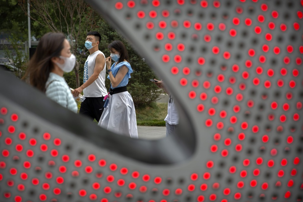 People wearing face masks to protect against the spread of the new coronavirus walk through a shopping and office complex in Beijing, Wednesday, June ...