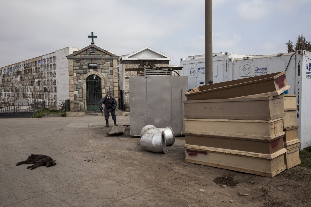 Funeral home worker Osvaldo Garcia, from Venezuela, cleans the area where used empty coffins of victims of COVID-19 are stacked after being cremated, ...
