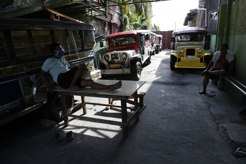 Driver Rey Escanilla, left, sits beside parked jeepneys at the Tandang Sora terminal which have been home for them since a lockdown started three mont...