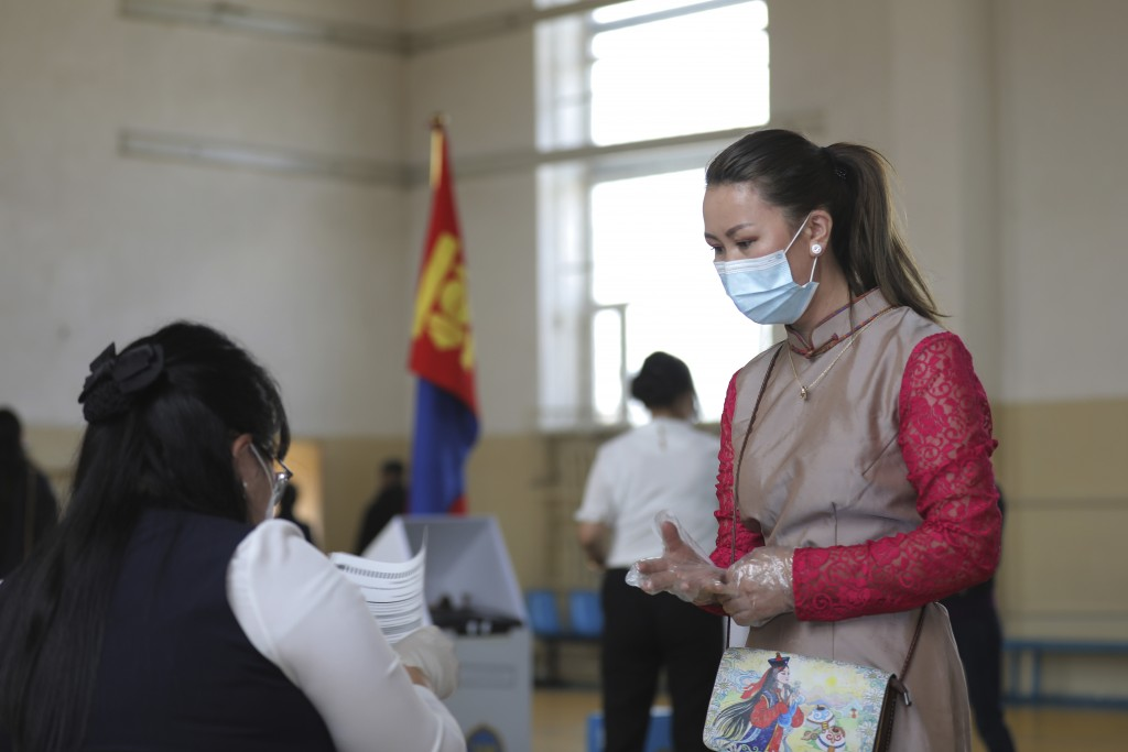 A woman wearing a mask waits to receive her ballot a polling station in Ulaanbaatar, Mongolia on Wednesday, June 24, 2020. Mongolians were voting in p...