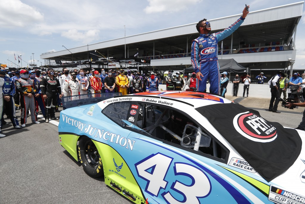FILE - In this June 22, 2020, file photo, Bubba Wallace takes a selfie of himself and of other drivers who had pushed his car to the front in the pits...