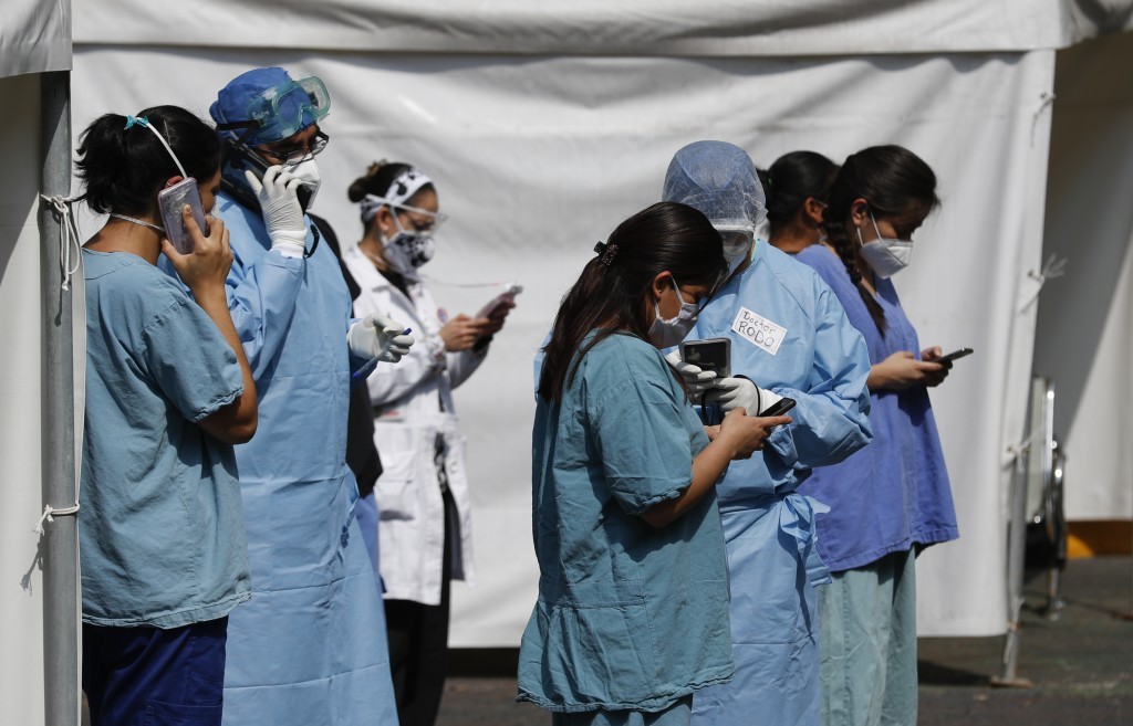 Health workers check their cell phones after an earthquake, outside the Juarez de Mexico public hospital in Mexico City, Tuesday, June 23, 2020. The e...