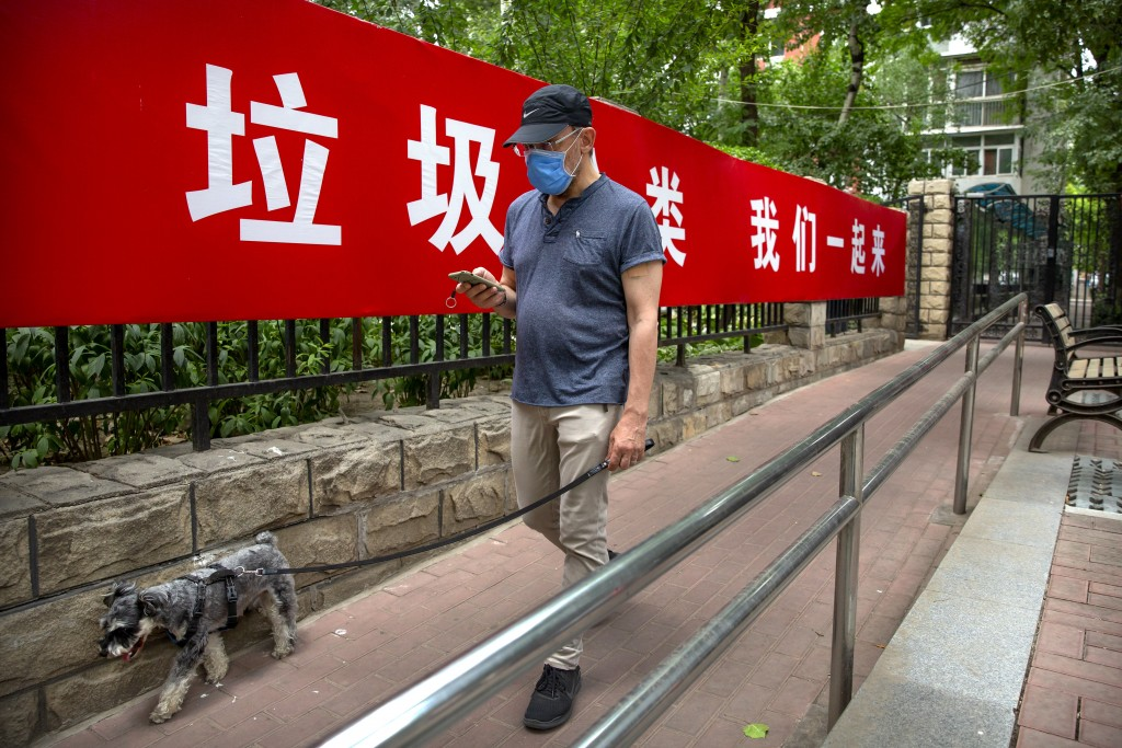 A man wearing a face mask to protect against the spread of the new coronavirus walks past a propaganda banner encouraging people to sort their garbage...