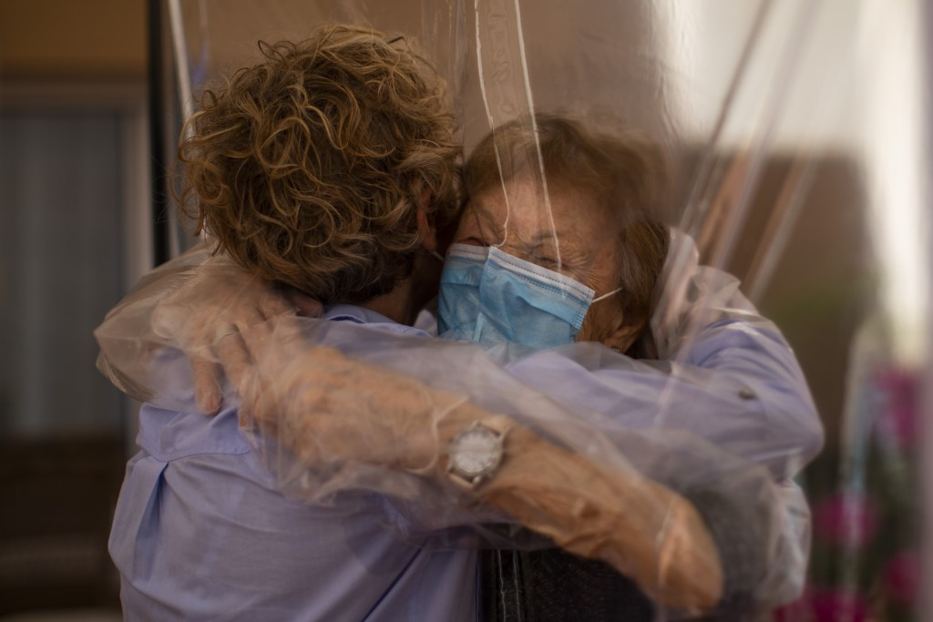 In this Monday, June 22, 2020 photo, Isabel Pérez López, 96, receives an embrace through a plastic film screen from her visiting daughter, Beatriz Seg...