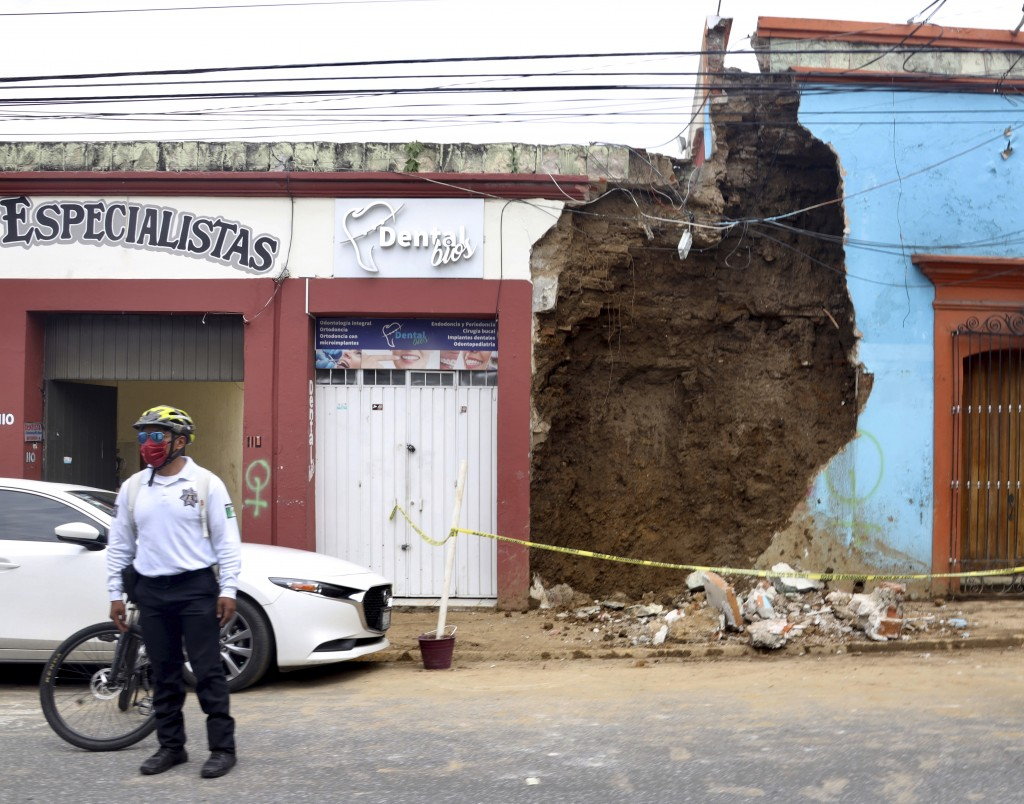 A policeman stands in front of a partially collapsed building after an earthquake in Oaxaca,, Mexico, Tuesday, June 23, 2020. The earthquake was cente...