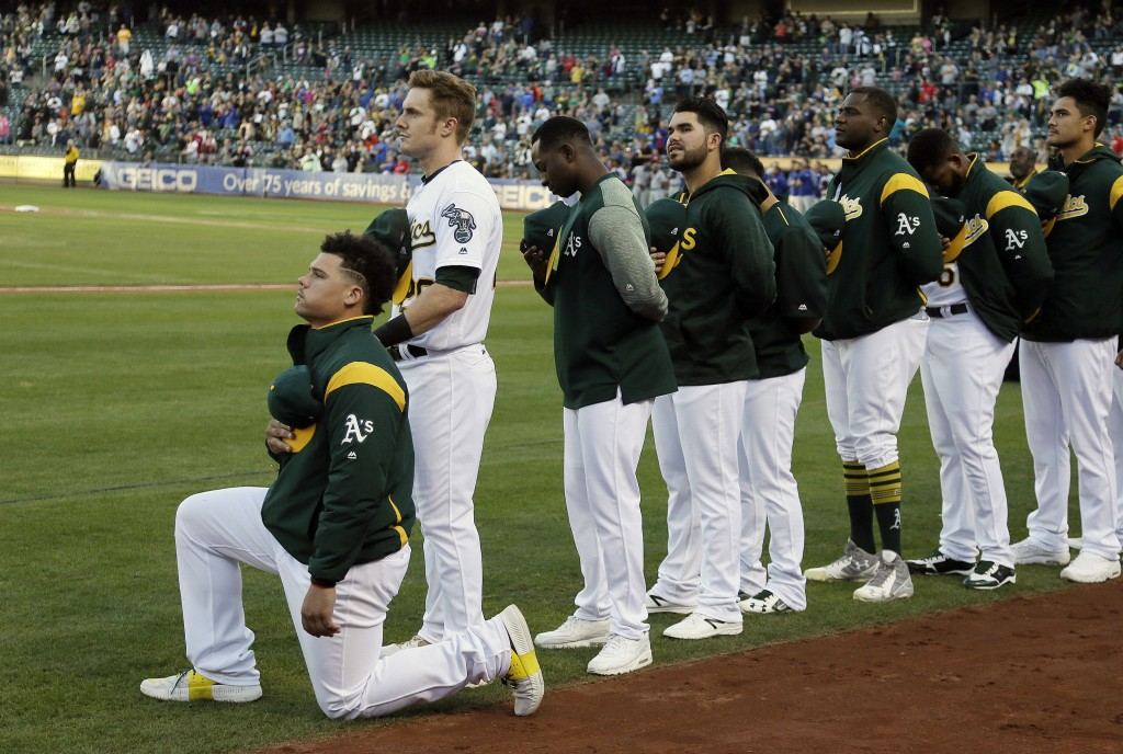 FILE - In this Sept. 23, 2017, file photo, Oakland Athletics catcher Bruce Maxwell kneels during the national anthem before the team's baseball game a...