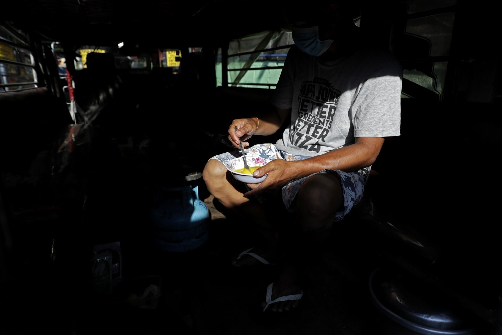 Driver Michael Navarra prepares egg to be cooked for their afternoon snack inside a jeepney at the Tandang Sora terminal which have been home for them...