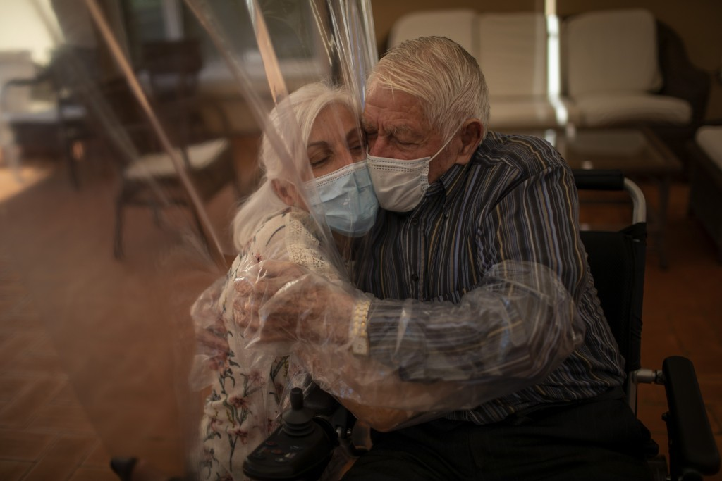 In this Monday, June 22, 2020 photo, Dolores Reyes Fernández, 61, hugs her father José Reyes Lozano, 87, for the first time in nearly four months as v...