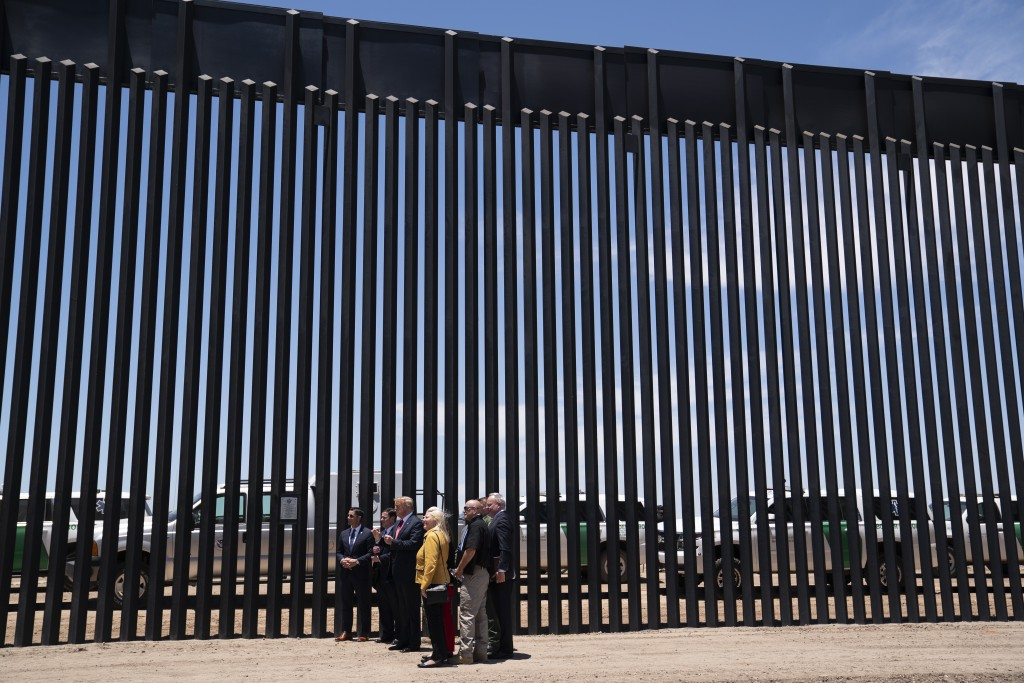 President Donald Trump poses for photos during a tour of a section of the border wall, Tuesday, June 23, 2020, in San Luis, Ariz. (AP Photo/Evan Vucci...
