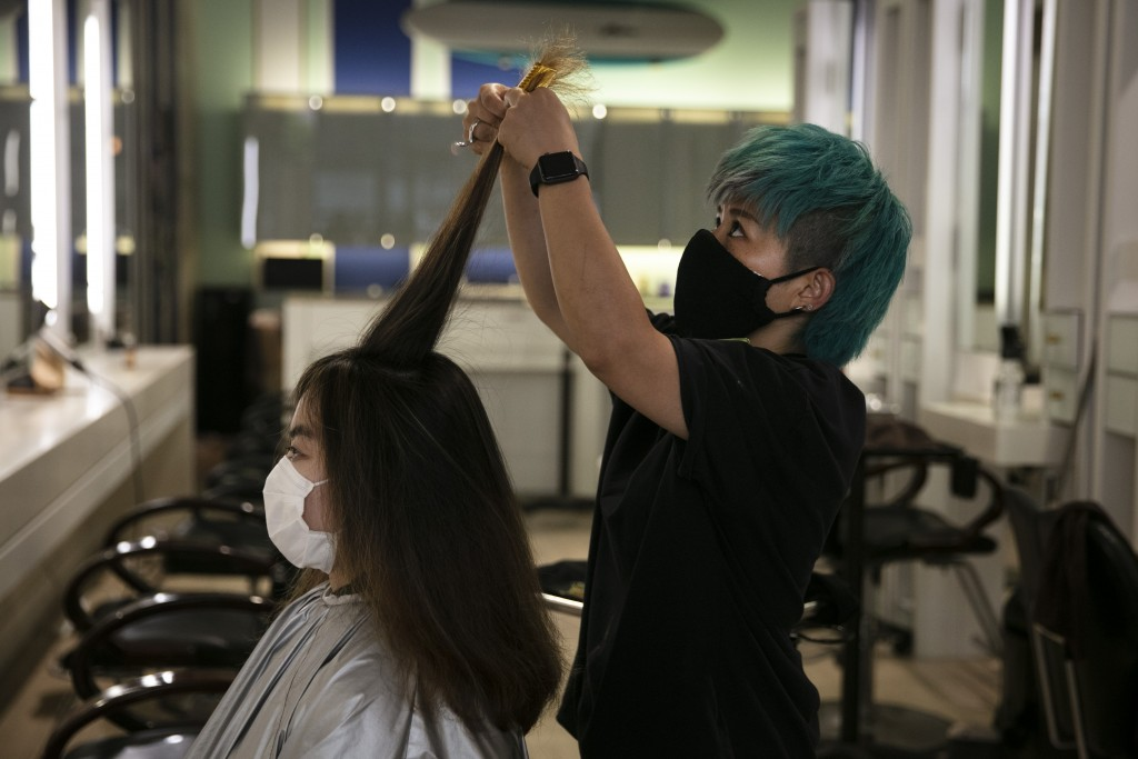 Zhongni Liu, left, gets a haircut from Akane Tachibana on Tuesday, June 23, 2020, in Santa Monica, Calif. The state Department of Public Health record...