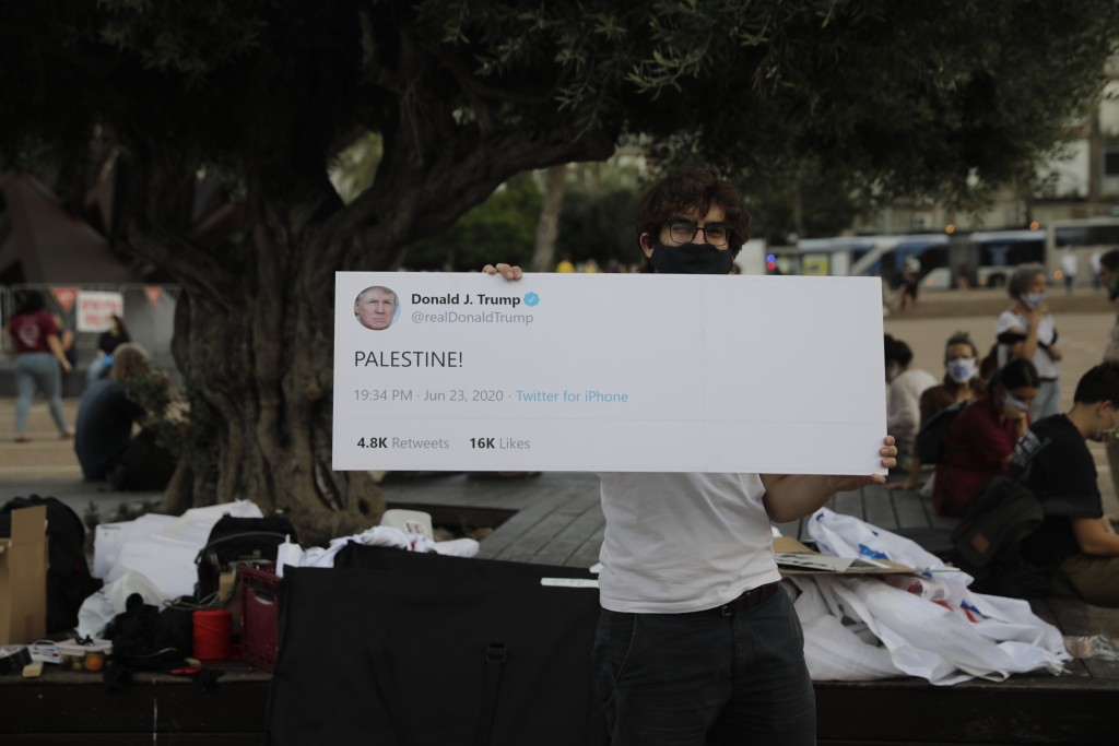 People take part in a protest against Israel's plan to annex parts of the West Bank and Trump's mideast initiative, in Tel Aviv, Israel, Tuesday, June...