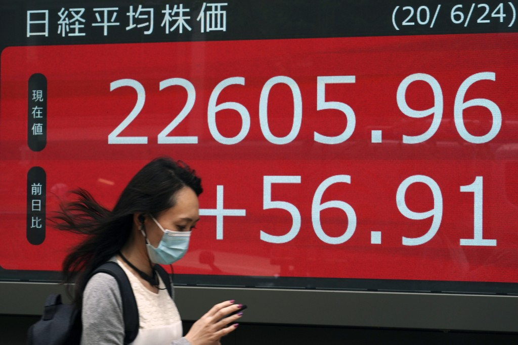 A woman walks past an electronic stock board showing Japan's Nikkei 225 index at a securities firm in Tokyo Wednesday, June 24, 2020. Asian shares wer...
