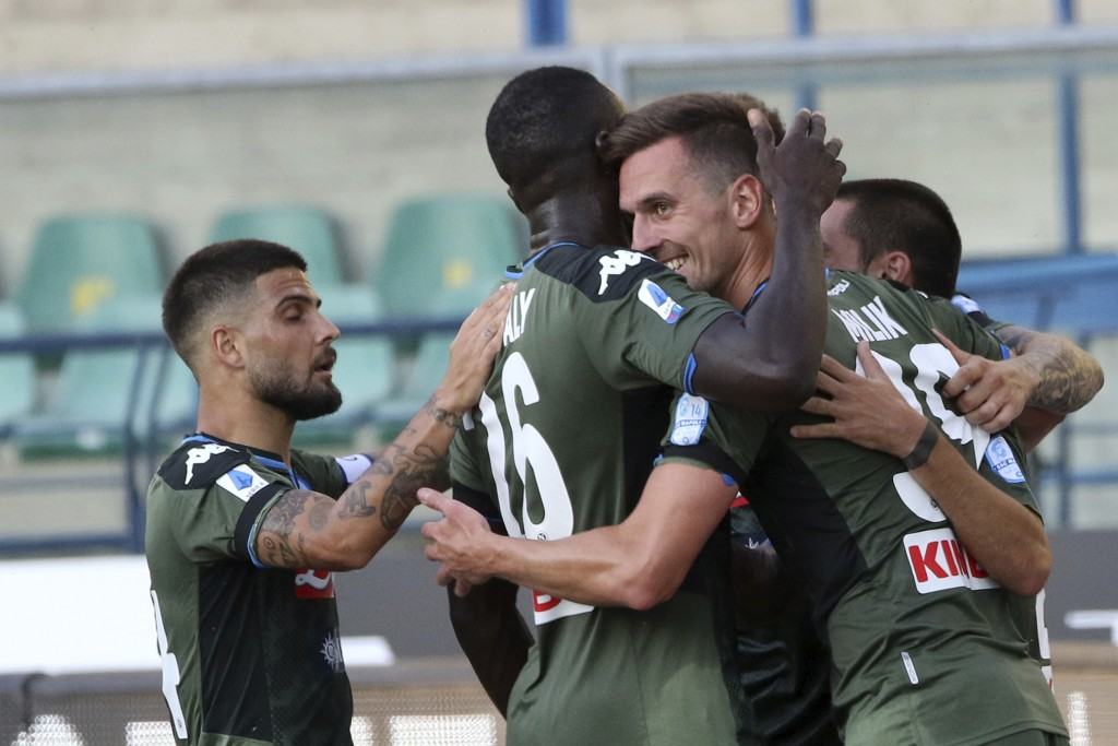 Napoli's Arkadiusz Milik, right, celebrates with teammates after scoring his side's opening goal during the Serie A soccer match between Hellas Verona...