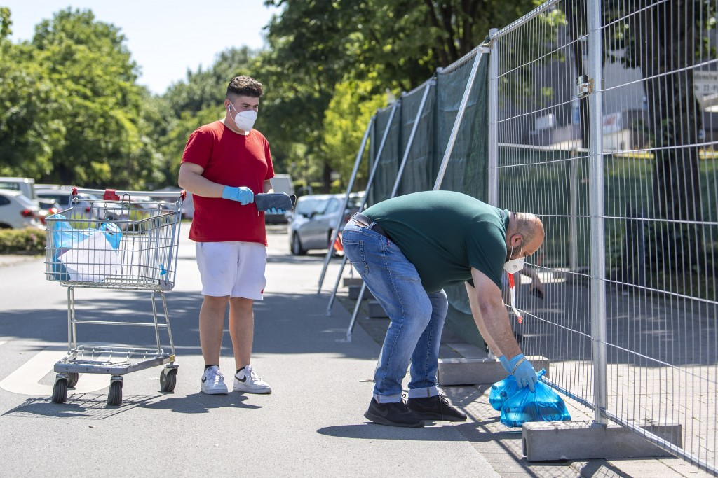 Employees of a grocery store deliver ordered products in plastic bags to residents of apartment buildings  that are partly under quarntine due to a ne...