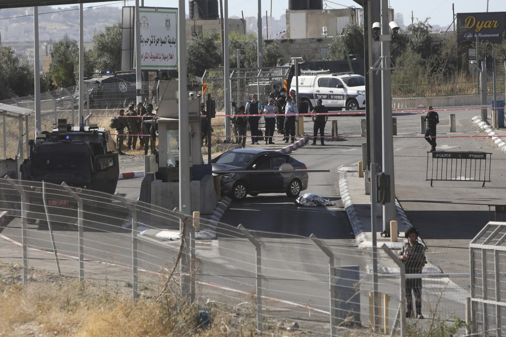 Israeli policemen stand around the body of a Palestinian at a checkpoint near Jerusalem, Tuesday, June 23, 2020. A Palestinian driver died Tuesday aft...