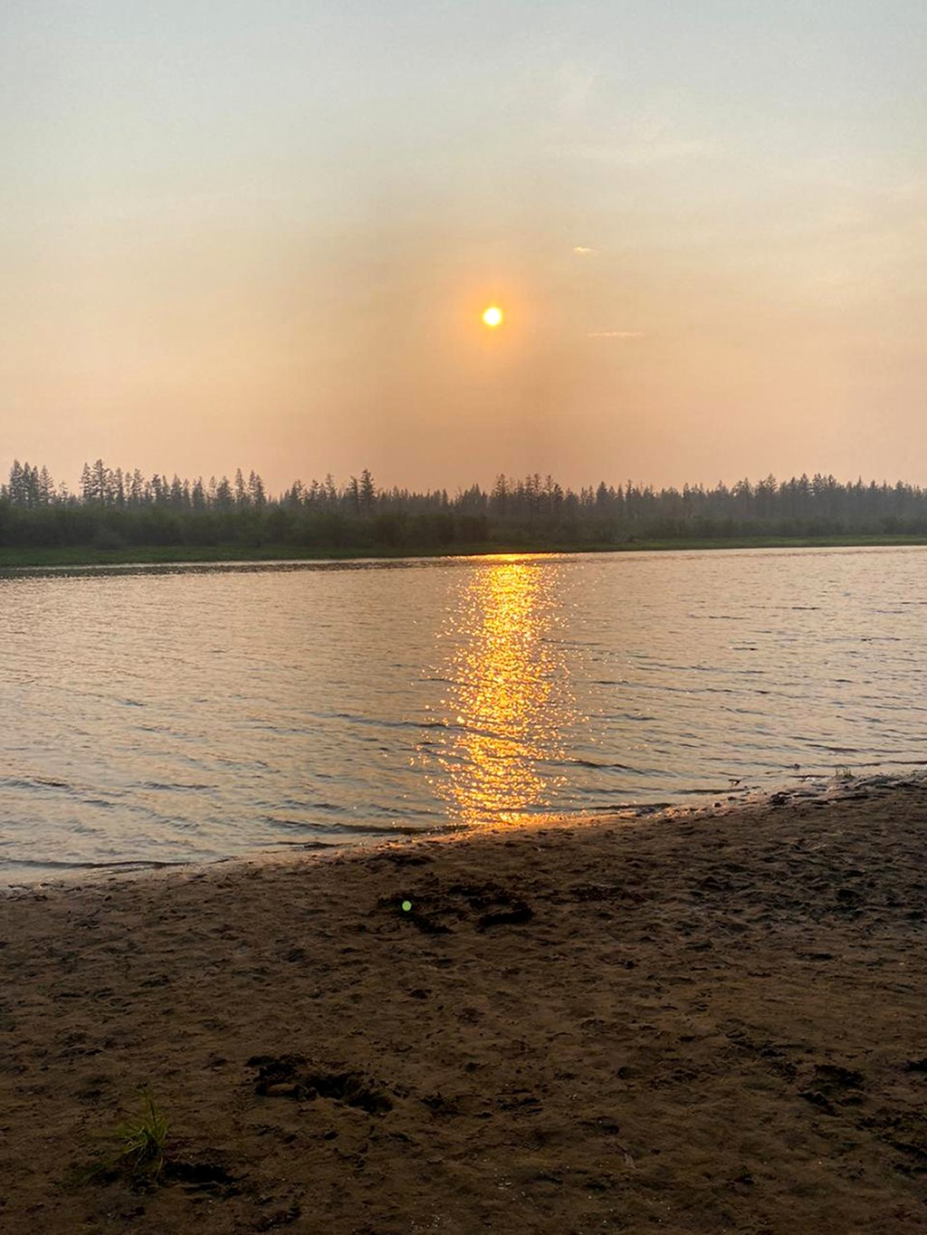 In this handout photo taken Tuesday, June 23, 2020 and provided by Olga Burtseva, a beach on the bank of Yana river is empty due to hot weather, durin...