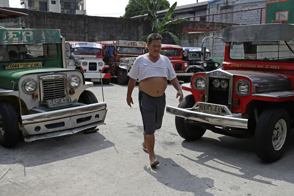 Driver Jude Recio walks past jeepneys parked at the Tandang Sora terminal which have been home for them since a lockdown started three months ago, on ...