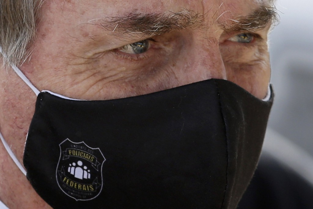 FILE - In this May 26, 2020 file photo, Brazil's President Jair Bolsonaro, wearing a face mask with a logo of the Federal Police, leaves his official ...