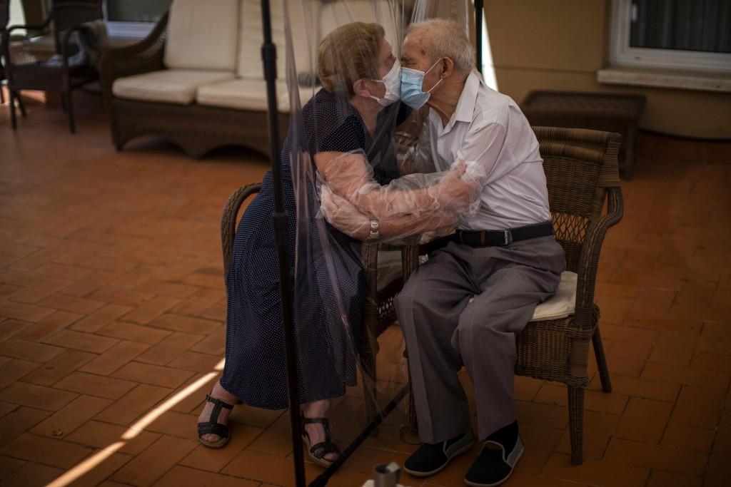 In this Monday, June 22, 2020 photo, Agustina Canamero, 81, and Pascual Pérez, 84, hug and kiss through a plastic film screen to avoid contracting the...