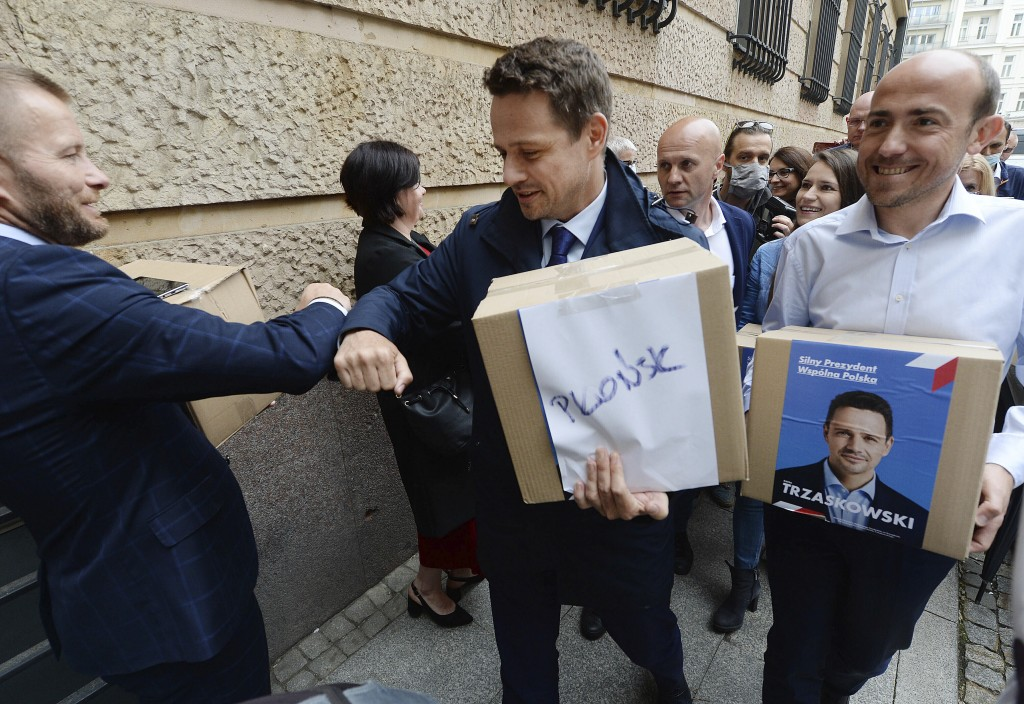 FILE - In this Tuesday June 9, 2020 file photo, centrist opposition presidential candidate, Warsaw Mayor Rafal Trzaskowski, center, greets a supporter...