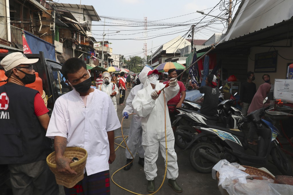 Members of Indonesia Red Cross spray disinfectant in an attempt to help curb the spread of the new coronavirus at a market in Jakarta, Indonesia, Wedn...