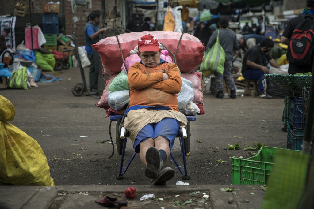 Porter Fernando Anaya, who begins his workday at 4 a.m., takes a nap as he takes a break from transporting vegetables, in La Parada market in La Victo...