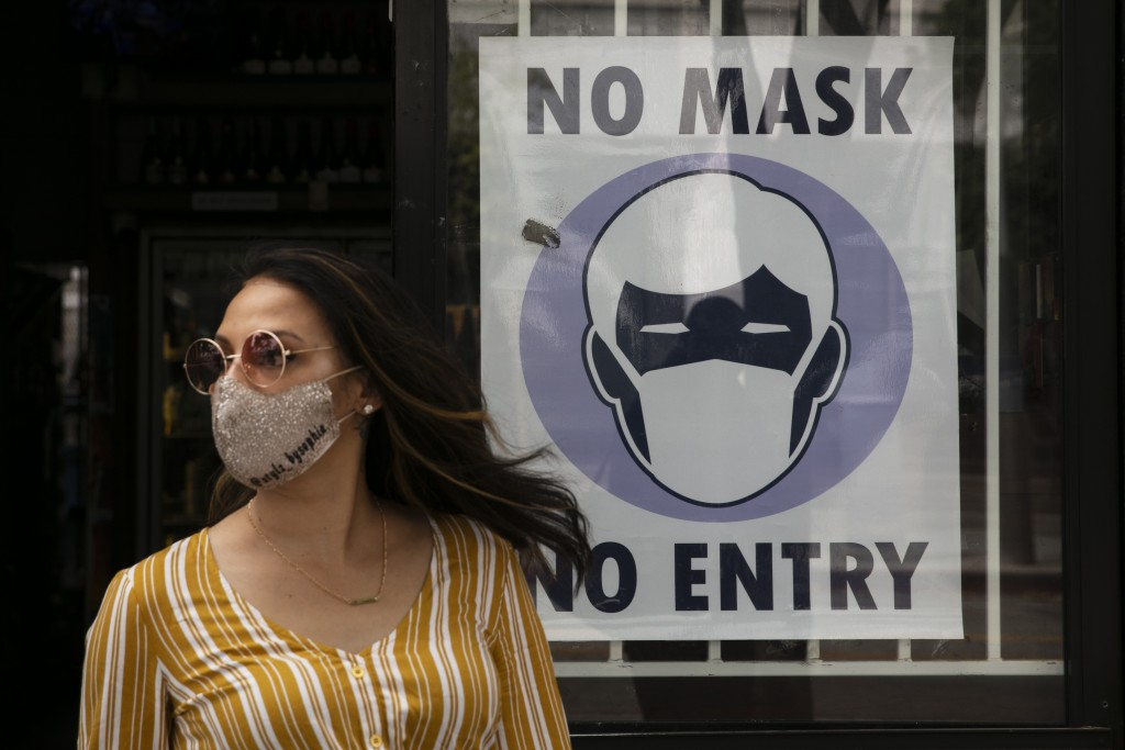 A woman walks out of a liquor store past a sign requesting its customers to wear a mask Tuesday, June 23, 2020, in Santa Monica, Calif. The state Depa...